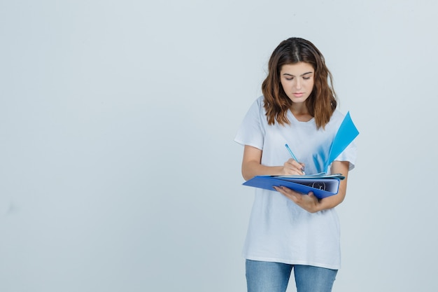 Young female taking notes on folders in white t-shirt, jeans and looking busy , front view.