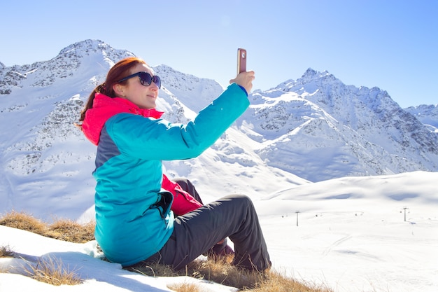 Young female taking a selfie on her phone on a beautiful mountain top. winter time