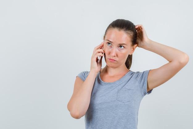 Giovane femmina parlando al telefono cellulare in maglietta grigia e guardando pensieroso. vista frontale.