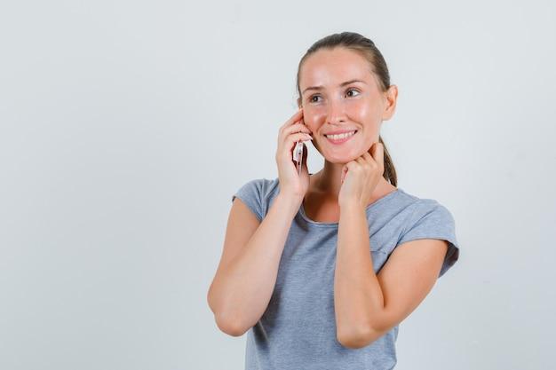 Молодая женщина разговаривает по мобильному телефону в серой футболке и выглядит весело. передний план.