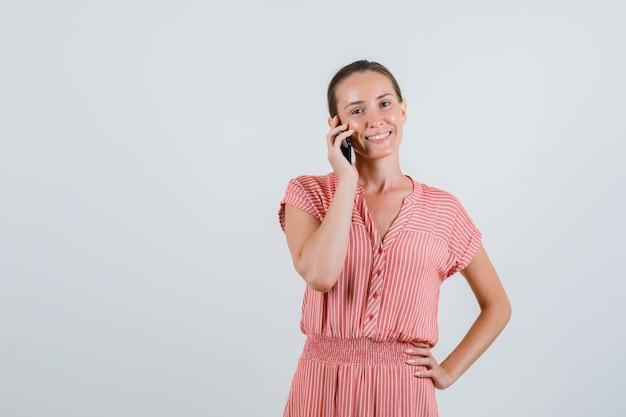 Молодая женщина разговаривает по телефону в полосатом платье и выглядит веселой, вид спереди.
