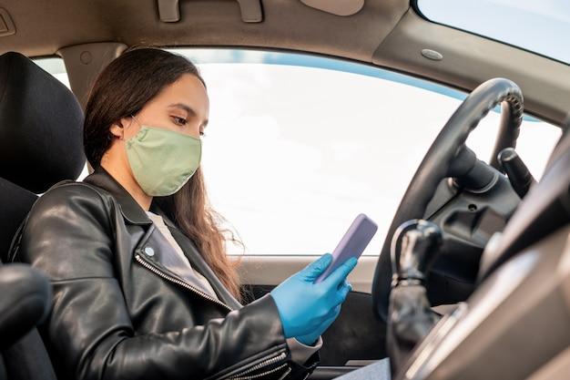 Молодая женщина-таксист в тканевой маске и перчатках сидит за рулем и использует приложение для смартфона службы такси