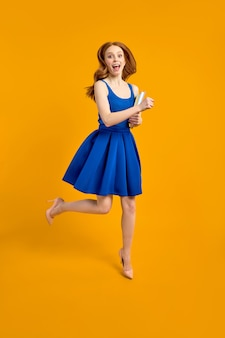 Young female teacher on blue dress enjoy working in school, jump holding books in hands, look at camera happily, isolated on yellow background