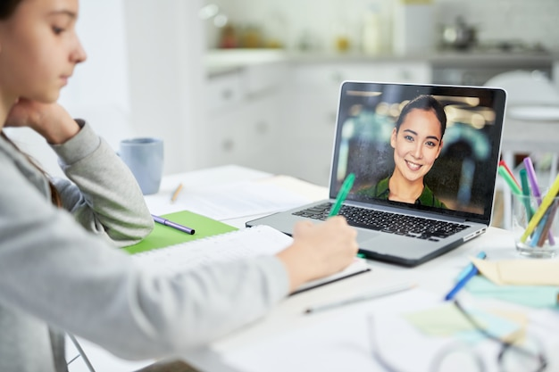 Young female teacher communicating with her student, using video chat app during online lesson. home schooling during quarantine. focus on laptop screen
