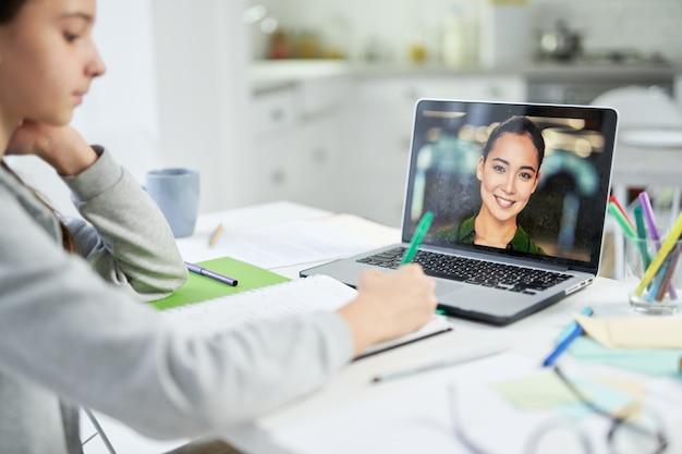 온라인 수업 중에 화상 채팅 앱을 사용하여 학생과 의사 소통하는 젊은 여교사. 격리 기간 동안 홈 스쿨링. 노트북 화면에 초점