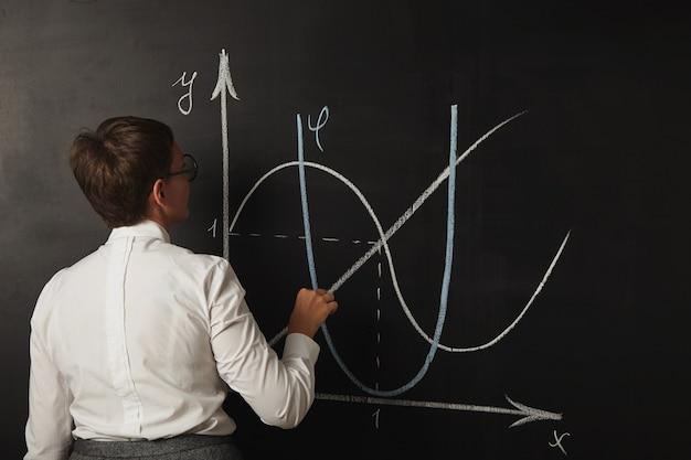 칠판에 수학 수업에 대한 그녀의 차트를 그리기 마무리하는 젊은 여성 교사