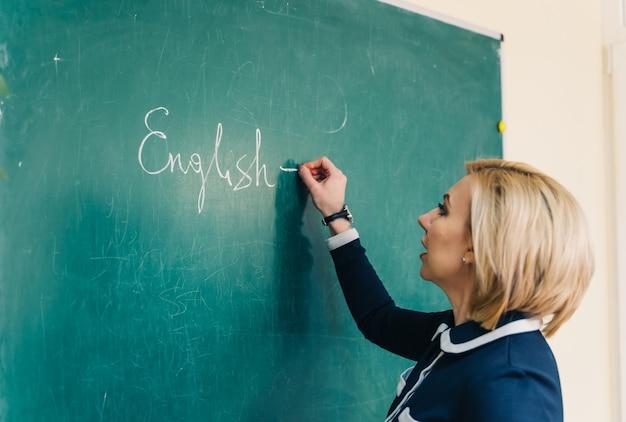 チョークを持って黒板に書いている若い女教師。教育プロセス。