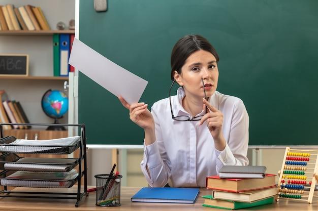 教室で学校の道具とテーブルに座ってメガネで紙を保持している若い女性教師