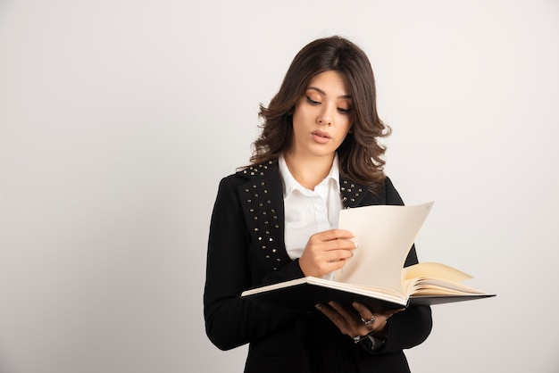 화이트 노트북을 통해 찾고 젊은 여성 교사.