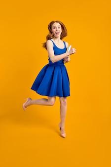 파란 드레스를 입은 젊은 여교사는 학교에서 일하는 것을 즐기고, 책을 손에 들고 점프하고, 노란색 배경에 고립되어 행복하게 카메라를 쳐다봅니다.