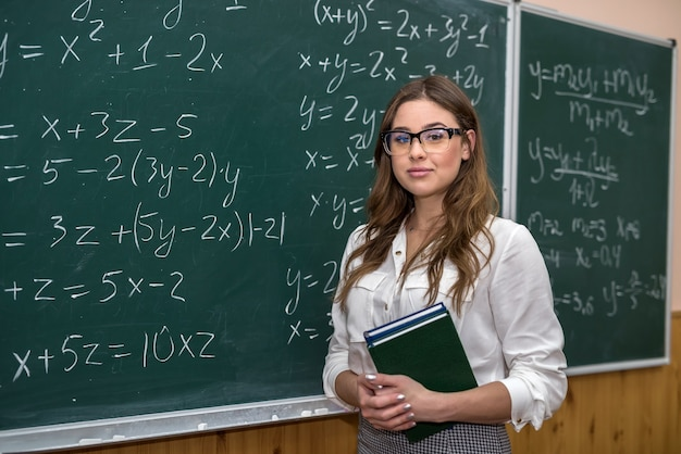 Young female teacher in the school room during class,  near chalkboard with writed  math formulas. education