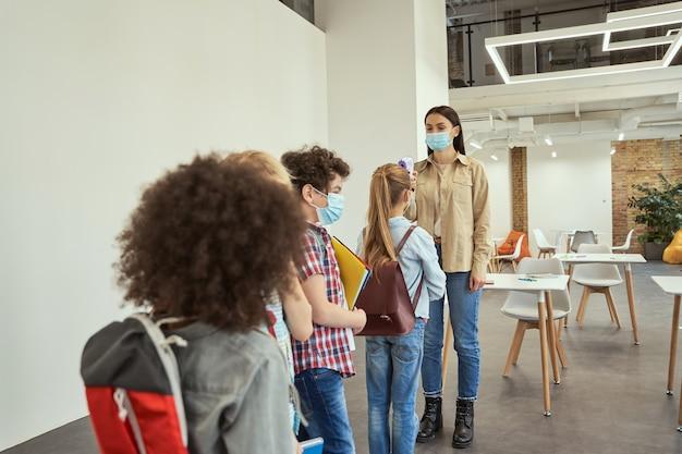 디지털을 사용하여 covid의 확산에 대한 열병에 대해 학교 아이들을 검사하는 젊은 여교사