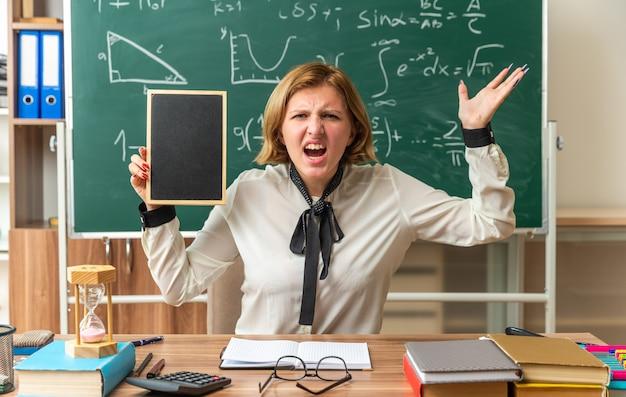 Giovane insegnante femminile si siede al tavolo con materiale scolastico tenendo mini lavagna in classe