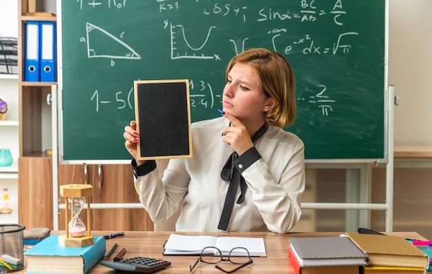 La giovane insegnante femminile si siede al tavolo con gli strumenti della scuola che tengono mini lavagna in classe