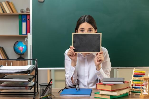 Giovane insegnante femminile seduta a tavola con gli strumenti della scuola che tengono e il viso coperto con mini lavagna in aula