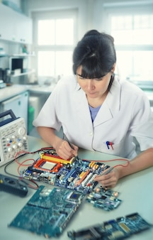 Young female tech or engineer repairs electronic equipment in research facility