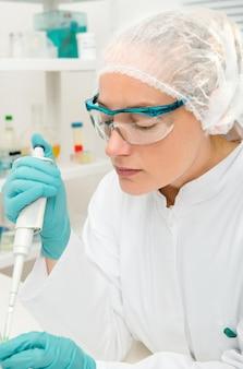 젊은 여성 기술 또는 과학자는 실험실에서 작동