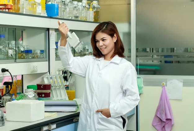 Young female tech or women asia scientist working with multichannel pipette in biological laboratory