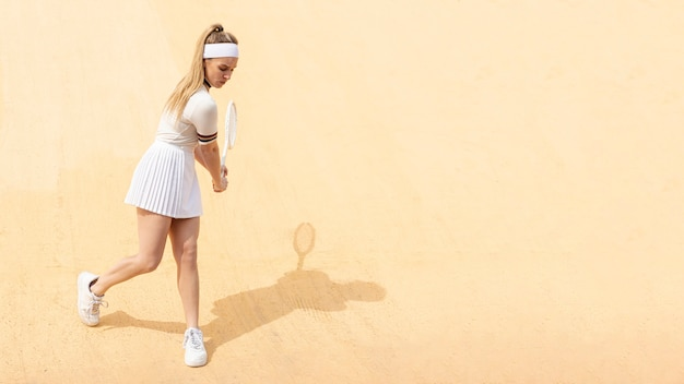 Young female tennis player hitting ball