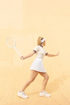 Young female tennis player running after ball