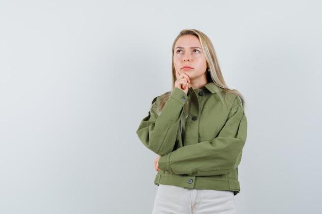 Молодая женщина думает в зеленой куртке и смотрит задумчиво. передний план.