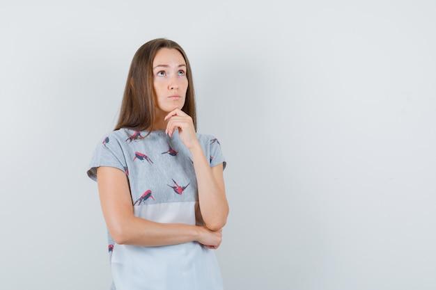 Tシャツを見上げて毅然とした表情で考えている若い女性。正面図。
