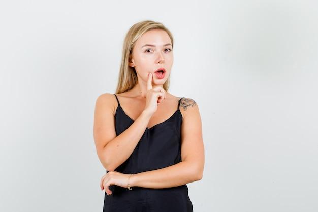 黒の一重項で口の近くで指で考える若い女性