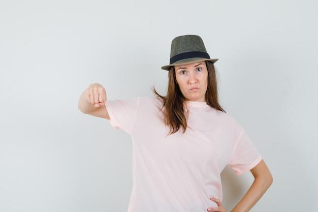 분홍색 티셔츠, 모자에 주먹으로 위협하고 심각한 찾고 젊은 여성. 전면보기.