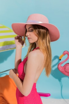 Young female touching hat and posing in pink swimsuit