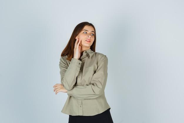 Giovane donna che si tocca la guancia mentre distoglie lo sguardo in camicia, gonna e sembra pensierosa, vista frontale.
