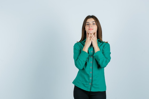 Young female touching her chin with fingers in green shirt, pants and looking cute , front view.