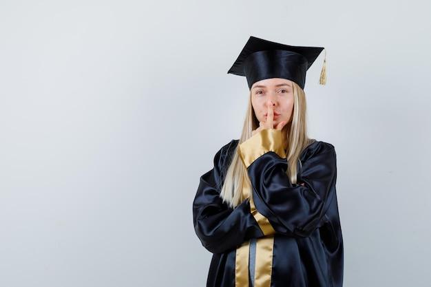 Молодая женщина трогает нос пальцем в униформе выпускника и выглядит мило
