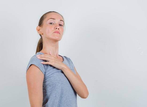Молодая женщина трогает плечо пальцами в серой футболке и выглядит серьезным, вид спереди.