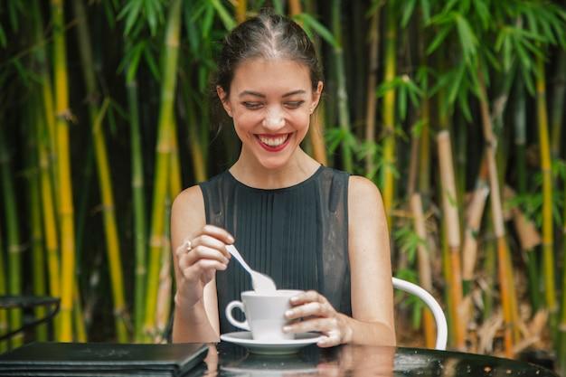 Молодой женский турист имея кофе снаружи