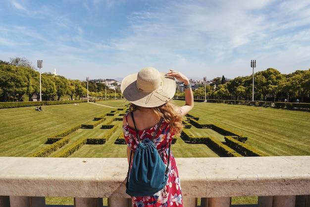 포르투갈의 햇빛 아래 에두아르도 7세 공원에서 붉은 꽃무늬 드레스를 입은 젊은 여성 관광객