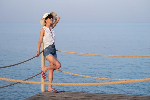 캐주얼 옷을 입은 젊은 여성 관광객이 해변에서 따뜻하고 화창한 날을 즐기고 있습니다. 여름 휴가 및 여행 개념입니다.