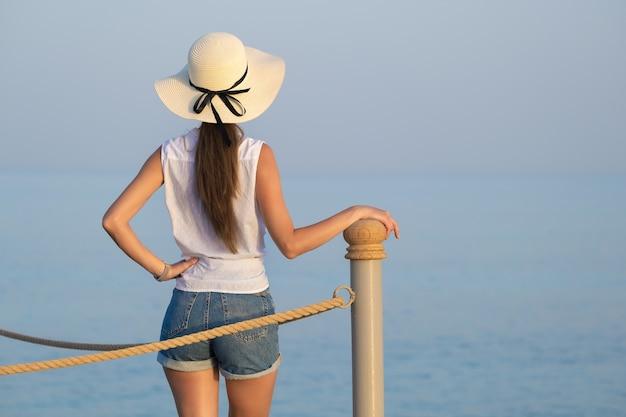 해변에서 따뜻하고 화창한 날을 즐기는 캐주얼 옷을 입은 젊은 여성 관광객.