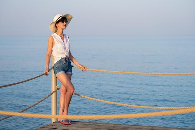 해변에서 따뜻하고 화창한 날을 즐기는 캐주얼 옷을 입은 젊은 여성 관광객