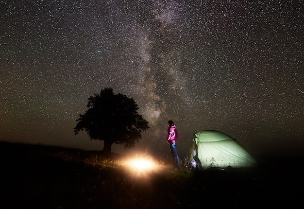 Young female tourist resting near illuminated tent, camping in mountains at night under starry sky