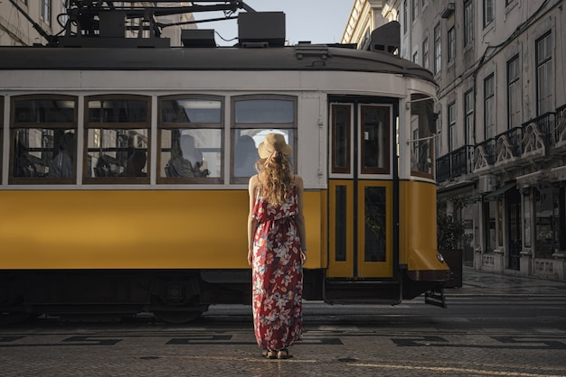 Young female tourist standing in front of a passing tramway surrounded by buildings at daytime
