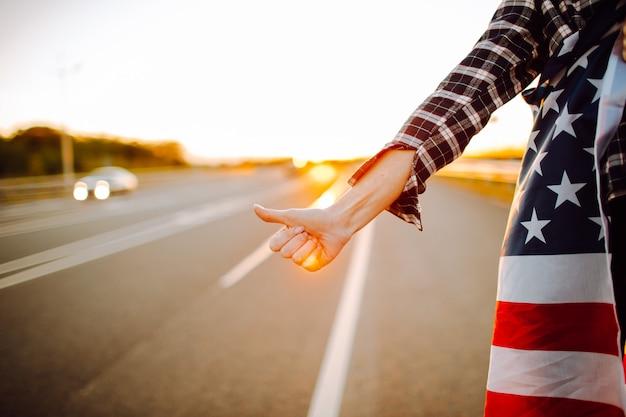 荒涼とした道に沿ってヒッチハイクするアメリカの国旗を持つ若い女性観光客