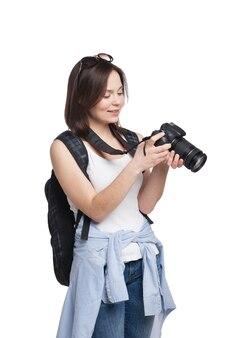 彼女のカメラを見ているバックパックを持つ若い女性の観光客。白で隔離