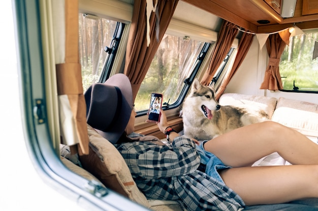 Молодая туристка со смартфоном фотографирует хаски внутри мобильного дома