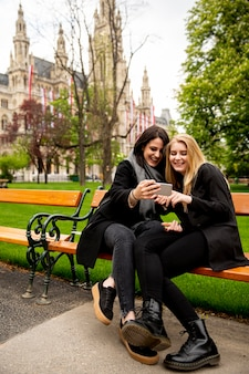 Young female tourists taking selfie with mobile photo on the bench in centre of vienna, austria
