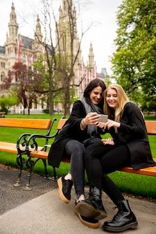 Молодые туристки, делающие селфи с мобильным фото на скамейке в центре вены, австрия