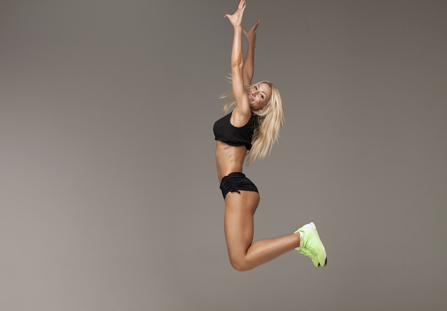 Young female in tracksuit jumping doing aerobics cardio exercises for losing weight and training strength, sportswoman doing leaps burning calories on pilates workout enjoying active lifestyle  l