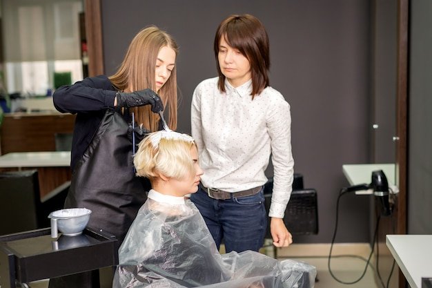 Юная ученица учится рисовать женские волосы под руководством профессионального парикмахера в парикмахерской.
