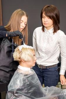 Молодая ученица учится рисовать женские волосы под присмотром парикмахера
