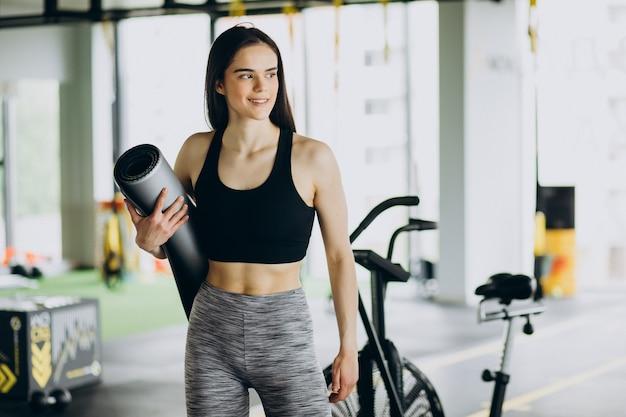 Молодая женщина-тренер, тренирующаяся в тренажерном зале