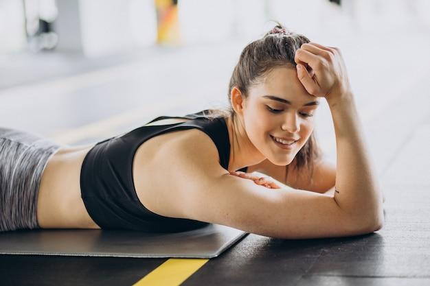 ジムで運動する若い女性トレーナー